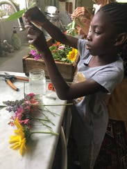 Kiriah, 7, arranges flowers she picked this week while