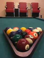 A pool table sits in front of a shoe shine station
