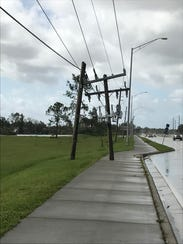 A utility pole is snapped in half on Immokalee Road