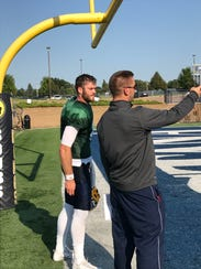 Augustana quarterback Ryan Rubley talks with offensive