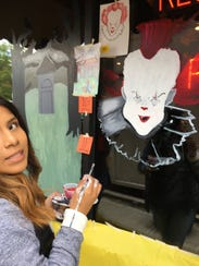 Evelyn Martinez, a 12th grade North Rockland art student, paints a clown on a business window.
