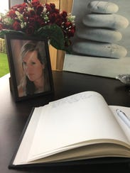 A book of condolence is open next to a portrait of
