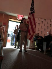 Military veterans carry flags into the auditorium at