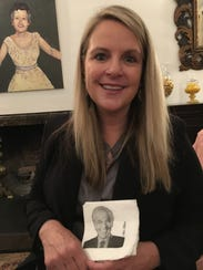 Hilary Newsom sits inside the living room of the recently renovated Ingleside Inn and holds napkins bearing the image of former owner, Mel Haber.