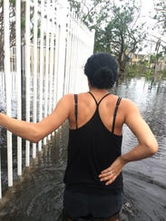 Marena Perez stands in thigh-high floodwaters after
