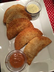 An appetizer of beef and chicken empanadas cost $10.