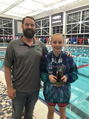 Megan Corcoran, 12, and her GPAC age division coach Greg Johnson, celebrate Corcoran's  five gold medal wins at the recent Southeastern Region Championships meet.
