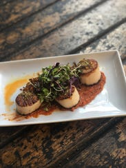 Scallops with Romesco are a specialty dish at Movida.