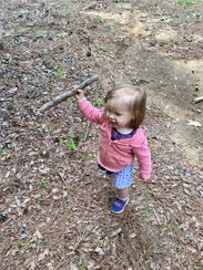 Marie Guidry, 1, finds a walking stick on a hike through