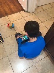 Sam Baig controls a cardboard car with the Nintendo