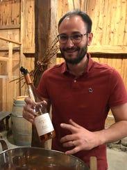 Sebastien LeSeurre holds a bottle of wine from Domaine