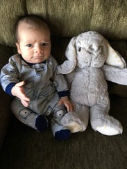 Delcan London sits with his stuffed bunny.