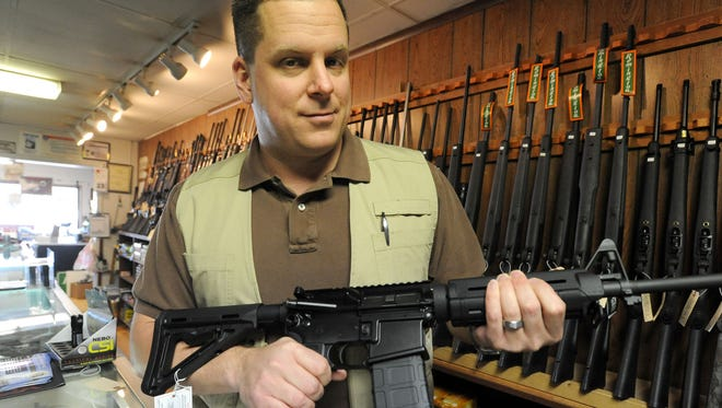 Ryan Allen, owner of Frontier Arms gun store in Cheyenne, Wyo., holds an AR-15 with a 30-round magazine. Allen said demand at his store has increased because of Colorado's new gun laws.