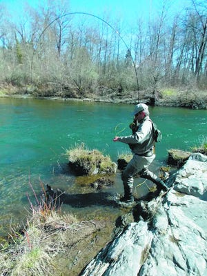 Mike Peters scrambles along the bank of the Applegate River, fighting a steelhead that took a fly in March of 2013.
