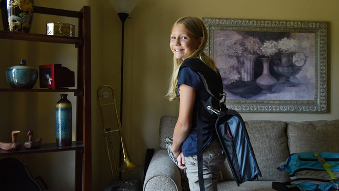 Allie Weber, a sixth grader at Edison Elementary School, invented a strap to carry her binder. The strap helps evenly distribute the weight of her books for easier carrying.
