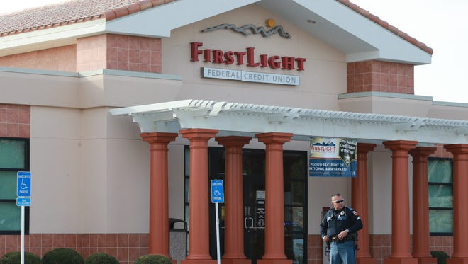 An El Paso police officer helps secure the scene after a robbery Monday at First Light Federal Credit Union, 1555 N. Lee Treviño.