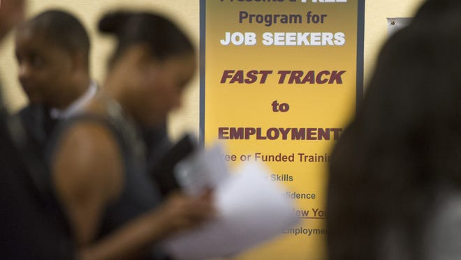 Job seekers line up to talk to recruiters during a job fair in Atlanta.