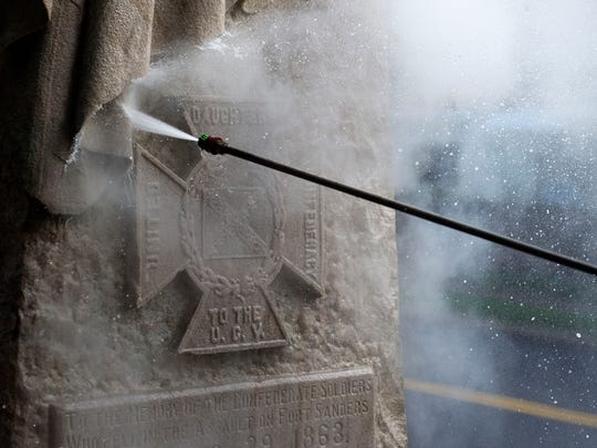 "Kevin Johnson, a public service foreman for the City of Knoxville, power washes a Confederate monument in Fort Sanders Wednesday, Aug. 23, 2017. The monument was defaced with paint one week ago, following the ""Unite the Right"" rally in Charlottesville, Virginia, which left three people dead."