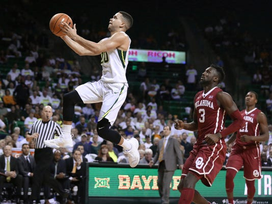 Baylor guard Manu Lecomte soars to the basket while scoring as Oklahoma forward Khadeem Lattin (3) watches during the second half of an NCAA college basketball game Tuesday, Feb. 27, 2018, in Waco, Texas. Baylor won 87-64. (Rod Aydelotte/Waco Tribune Herald via AP)