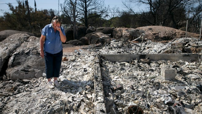 Judy Aldridge, a resident of Glen Ilah, looks at the debris of what was her home on Wednesday, July 10, 2013. The home was destroyed in the Yarnell Hill Fire.