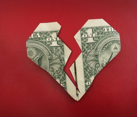 a dollar folded into a heart shape and then cut almost in half, looking like a broken heart