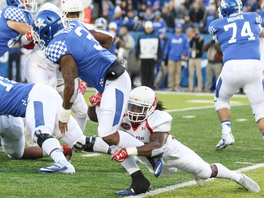 Austin Peay sophomore Juantarious Bryant (26) tackles Kentucky runningback Jojo Kemp (3) during their game at Commonwealth Stadium on Saturday. Austin Peay lost the game 49-13.