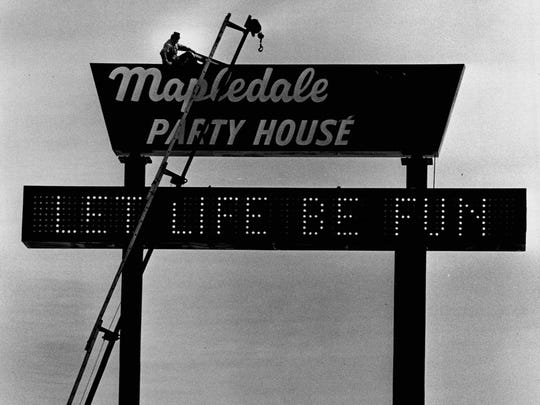 Routine maintenance is performed on the Mapledale Party House after a windstorm in 1979. The 60-foot sign overlooking Interstate 490 was a landmark for many motorists.