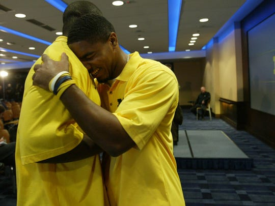 """Fifth year senior Willis Barringer (facing) hugs teammate David Harris during a press conference Monday November 13, 2006 at the Junge Family Champions Center on the campus of U-M before the big game between Michigan and Ohio State. Barringer had just told a reporter who asked what he thought of Ohio State coach Jim Tressel having U-M coach Lloyd Carr's number (figuratively). Barringer replied, """"Maybe he should give him a call sometime."""""""