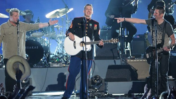 U.S. Marine Corps Staff Sgt. Brandon Valentine, center, and from left, Gary LeVox and Jay DeMarcus, of the musical group Rascal Flatts, perform at ACM Presents an All-Star Salute to the Troops on Monday, April 7, in Las Vegas.