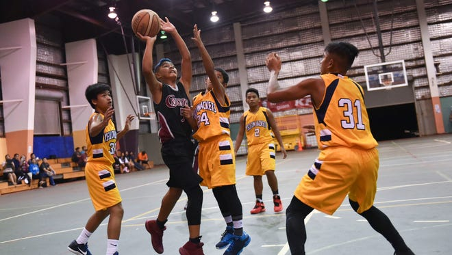 In this file photo, the Yellow Jackets play Crusaders Red in the Guam Youth Basketball Association Under-12 Division championship game at the Astumbo Gym.