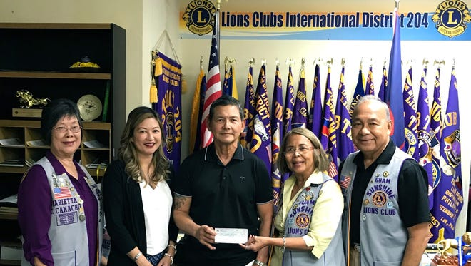 """During the general membership meeting of the Guam Sunshine Lions Club on Oct. 17, special guests Jessica Cate-Certeza (2nd from left) and Joseph Certeza, (3rd from left) presented a donation of $1,000 to the club in honor of Certeza's late mother, Josefa """"Tan Pai"""" Certeza, had been a recipient of the club's """"Caring for the Sick and the Elderly"""" service project. Lion Rosie Matsunaga, club president (4th from left), accepted the check. The Certezas were guests of Lion Marietta Camacho, (far left), and Lion Pete Babauta, (far right)."""