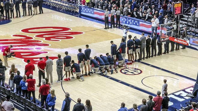 Mississippi basketball players take a knee during the national anthem before an NCAA college basketball game against Georgia in Oxford, Miss., Saturday, Feb. 23, 2019.