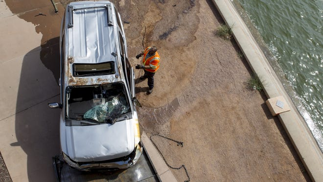 A worker prepares to tow a vehicle after it crashed into Tempe Town Lake on Sunday, Oct. 18, 2015 in Tempe, AZ. Four people who were in the car were pronounced dead.