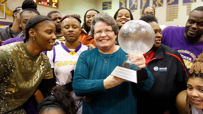Former Milwaukee Washington high school girl's basketball coach Pam Kruse is surrounded by current and former players in a ceremony honoring Kruse.