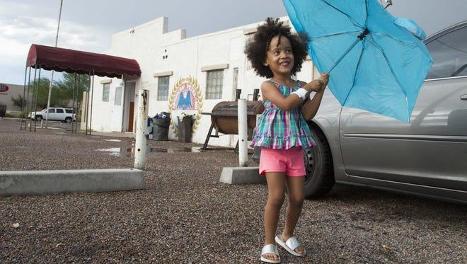 Lenaeyah Lstrl, 4, celebrates her fourth birthday in the rain in Phoenix on Aug. 3, 2017.