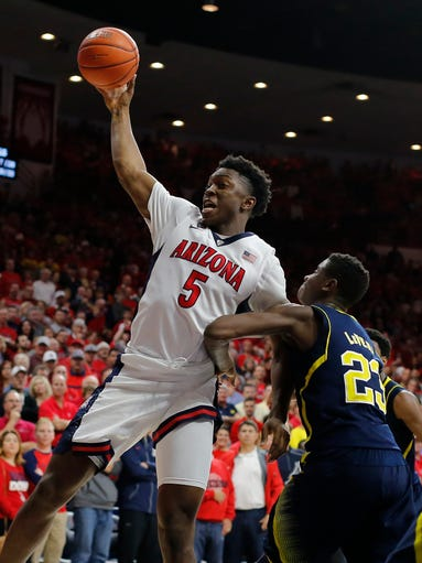 Arizona forward Stanley Johnson (5) rebounds on Michigan