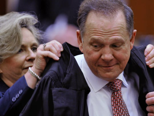 Kayla Moore helps her husband, Alabama Supreme Court Chief Justice Roy Moore, into his robe during his swearing-in ceremony Friday at the Alabama Supreme Court PHOTOS BY LLOYD GALLMAN/ADVERTISER Kayla Moore, left, helps her husband Alabama Supreme Court Chief Justice into his robe during Investiture ceremonies at the Alabama Supreme Court on Friday, Jan. 11, 2013. (Montgomery Advertiser, Lloyd Gallman)