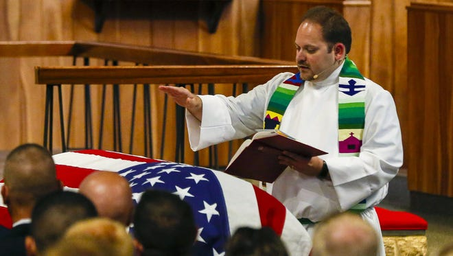 The Rev. Bryan Lagerstam stands next to the casket of Senior Airman Drew Bellairs as he gives the final blessing Thursday, Aug. 6, 2015, during the airman's funeral service at Our Savior's Lutheran Church in Osage, Ia.