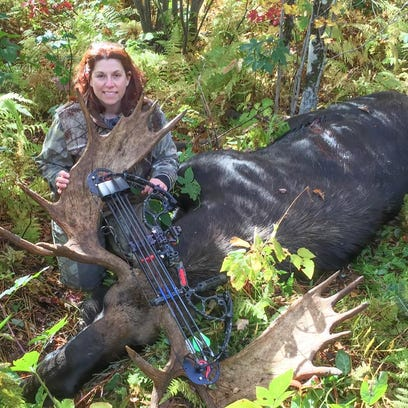 Tammy Miller of Fairfax with the 931-pound bull moose she took in Norton on the second day of Vermont's archery moose season. Her bull topped the previous archery record 919-pound moose taken last year