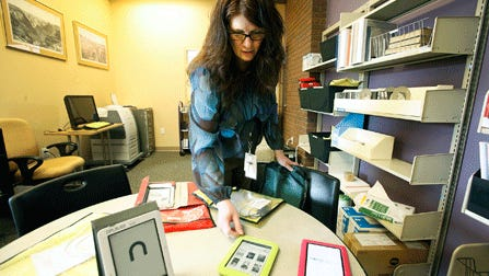 Librarian Sandy Irwin displays e-readers that can be checked out of the Durango, Colorado public library.