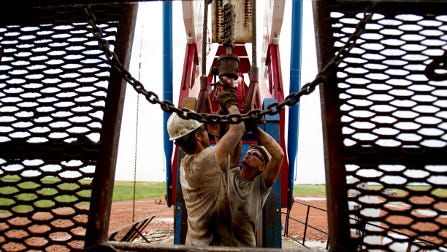 Workers toil on an oil derrick outside of Williston, N.D. West Virginia sent a delegation to North Dakota last week to learn more about its savings account for oil and gas revenues.