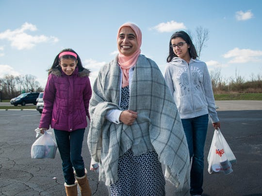 Afreen Asif and her volunteers carry bags of dry foods during a Rahma food drive at the Islamic Center of Greater Cincinnati on March 20.