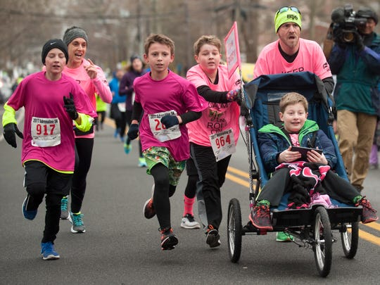 10-year-old Andrew Sylvester, an autistic 5th grade student at the West End Memorial Elementary School in Woodbury,  approaches the finish line while being pushed by West End Memorial Elementary School Principal Vincent Myers and Andrew's twin brother, Austin, a 5th grade student at the West End Memorial Elementary School, as they are joined by, (from left), Stacey Augustine (Andrew's school social worker), and West End Memorial Elementary School 5th grade students Peyton Shute, Charlie Floyd, and Sebastian Falcone during the Haddonfield Adrenaline 5K on Saturday.  The group took part in the race to raise awareness of people with special needs, and is part of the school's drive to be welcoming and inclusive. 03.18.17