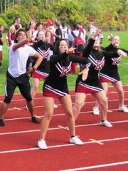Aries Sanchez, rear left, is the student inside the uniform of Elmira High School's mascot, the Conductor. He is also a member of the cheerleading squad, shown here.