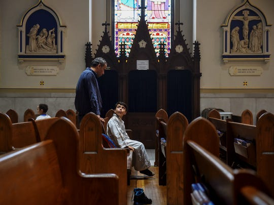 """Samuel Sadek of Hellam Township, left, speaks to his son Peter, 9, near the end of a Coptic Orthodox service Saturday, July 29, 2017, at St. Mary's Catholic Church in York. Coptic boys, wearing white robes called """"tonias,"""" serve as deacons during the service. About 60 Egyptian Coptic Christian families have moved to York County in recent years to escape religious persecution in Egypt."""