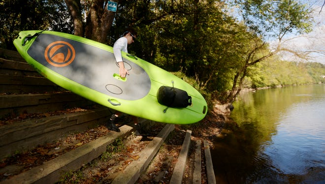 Kyle Ellison, owner of Wai Mauna Asheville SUP Tours, takes a paddle board into the French Broad River October 6, 2016.