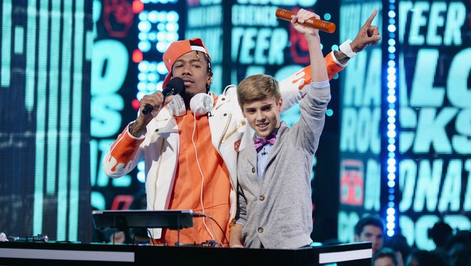 Rapper and actor Nick Cannon, left, and Caleb White of Northville on stage at the Nickelodeon HALO Awards at Pier 36 on Nov. 4 in New York City. The show will air at 7 p.m. Sunday on Nickelodeon.