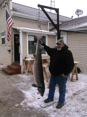 Gregory Naparalla of Berlin shows the sturgeon he harvested on Sunday.
