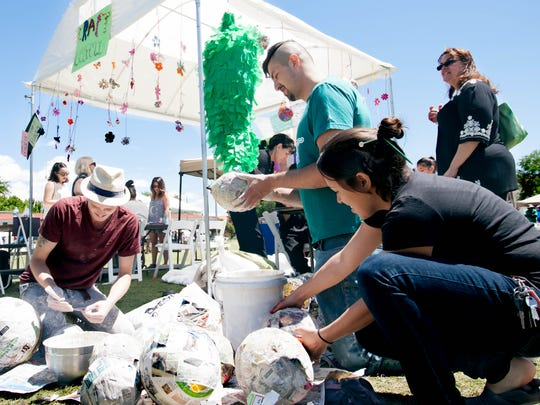 Dylan Schultz, left, Jose Arenivar and Taylor Reed of the History of Craft class make recycled piñatas for the community at the Craft Culture booth during the Earth Day celebration at New Mexico State University  on Sunday.
