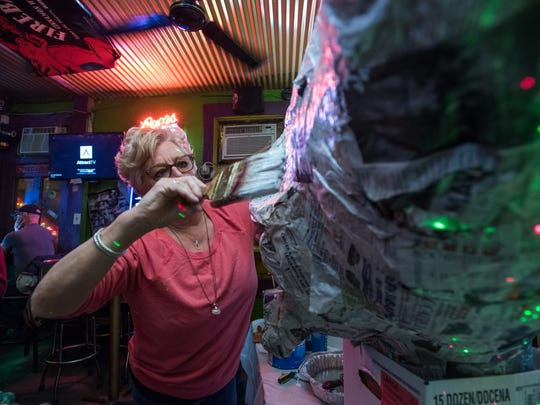 Amy Kummler of Covington, works on a big head at the Up Over bar in early February for the Covington Mardi Gras Grand Parade on Feb. 25.